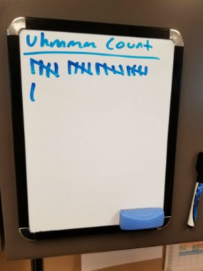 """Small desktop whiteboard with tally marks for an """"um"""" count on sales calls"""